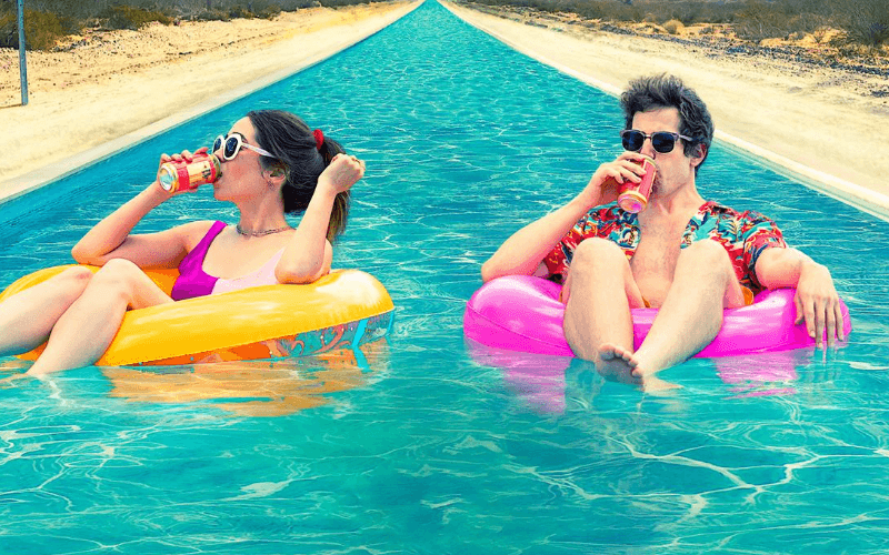 Image: Cristin Milioti and Adam Sandburg in a pool drinking beer.