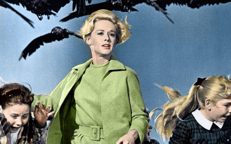 Still from Alfred Hitchcock's film the Birds: Tippi Hedren fleeing from some awesome crows along with two children.