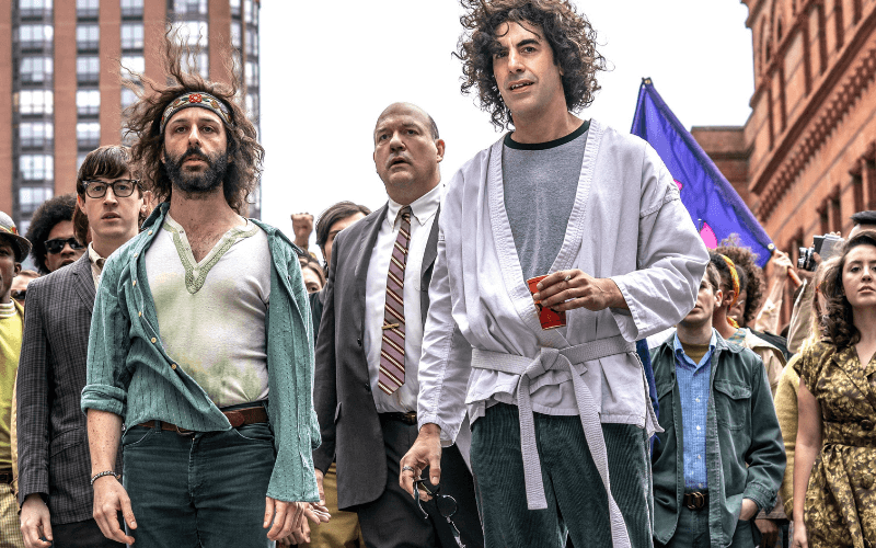 Alex Sharp, Jeremy Strong, John Carroll Lynch and Sacha Baron Cohen backed by a wall of protesters in the Trial of the Chicago 7